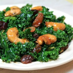 Kale Salad with Sugar-Coated Cashews Recipe - This kale salad is dressed with soy sauce and tossed with raisins and sugar-coated cashews for a delicious summer treat.