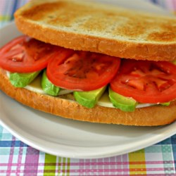 Delicious Avocado Sandwich Recipe - A quick and easy lunchtime favorite, this recipe for an avocado sandwich is topped with tomato, cheese, and balsamic vinegar.