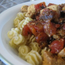 Chicken Pasta II Recipe - Chicken breast is cooked with bacon, tomatoes and wine, then spooned over steaming radiatore pasta.