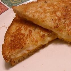 Cheesy Grilled Cheese Recipe - This is my version of the best grilled cheese inspired by a local restaurant in DC. Rye bread is broiled with three types of cheese then pressed together to make a masterpiece of a hot sandwich.