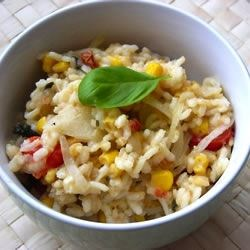 Risotto with Tomato, Corn and Basil Recipe - This is a labor of love, lots of stirring and timing to get all the ingredients added and the risotto creamy and wonderful. But, it's well worth it. When it's ready, a sprinkling of Parmesan cheese and slivers of basil finish it perfectly.