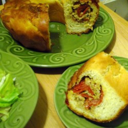 Sausage Bread Recipe - This is the full-meal deal. Prepare packaged bread mix and jelly-roll it around a hearty filling of pork sausage, pepperoni, mozzarella, Parmesan, Cheddar and herbs.  This makes a great lunch all by itself or with a salad.