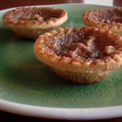Mom's Butter Tarts Recipe - Prepared pastry is cut into 3-inch rounds and fitted into tiny tart shells and chilled. The filling is made with golden syrup, eggs, butter, brown sugar, raisins and a dash of cinnamon. This yummy concoction is then spooned into each tart shell and baked in a very hot oven until golden. This recipe yields 24 tasty tarts.