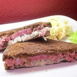 Reuben Sandwich I Recipe - Rye bread filled with corned beef, sauerkraut and mozzarella and fried in a skillet until hot and gooey.