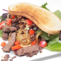 Tongue and Mustard Sandwiches Recipe - Beef tongue and onions are simmered until tender, then sliced and stuffed into a scooped-out loaf of dark rye bread with country-style mustard. The loaf is cut into sandwiches.