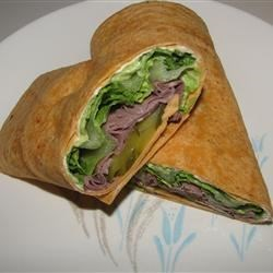 Roast Beef and Avocado Wraps Recipe - Tomato-herb tortillas layered with a cumin-garlic cream cheese spread, deli roast beef, lettuce, cubed avocado and tomatoes, and grated Colby-Jack cheese makes a totally satisfying wrap.