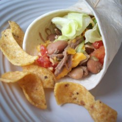 Pork Chalupas Recipe - A simple slow cooker meal! Pork roast is cooked all day with pinto beans in a seasoned sauce then shredded. Serve on tortillas with sour cream, salsa, and cheese or your favorite toppings.