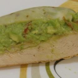 Guacamole Chicken Melt Recipe - Seasoned chicken breasts are browned in butter and olive oil, topped with homemade guacamole and slices of pepper jack cheese, then broiled.