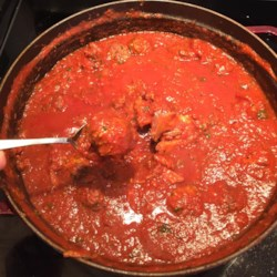 North End Sunday Gravy Recipe - This is a long-simmering homemade Italian 'gravy' with meatballs, featuring a savory herbal taste thanks to the addition of basil, mint, and red pepper flakes.