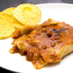 Taco Lasagna Recipe - Frilly lasagna noodles are layered with Cheddar cheese and a meaty tomato sauce flavored with taco seasoning. Microwave this tasty casserole, and top with a crunchy layer of tortilla chips.