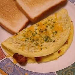 Crispy Bacon and Sweet Onion Omelet Recipe - Sauteed onions, crispy bacon, and a blend of cheddar and American cheeses provide the filling for this fluffy omelet.