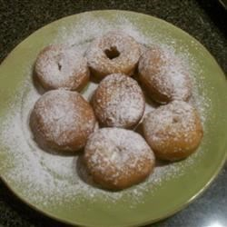 Kneecaps Recipe - This small, sweet fried doughnut has an indent in the center, rather than a hole. It's then covered with powdered sugar and filled with whipped cream. Add a few sprinkles or sugars for a decorative touch.