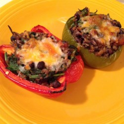 Stuffed Peppers with Quinoa Recipe - Stuffed red bell peppers made with quinoa, black beans, and spinach are a colorful, whole-grain side dish.