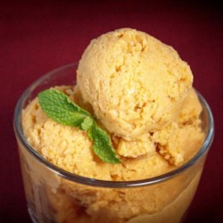 Pumpkin Frozen Yogurt Recipe - A light and tangy frozen pumpkin yogurt dessert is sweetened with maple syrup and spiced with cinnamon, nutmeg, and cloves.