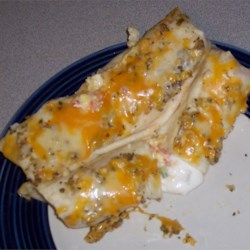 Wrapped Mexican Eggs Recipe - A flour tortilla is topped with a tomato/egg/cheese filling and sour cream, rolled up, and the whole casserole-full is doused in an incredible tomatillo salsa and baked.