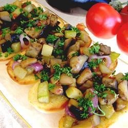 Veggie Delight on Garlic Bread Recipe - Classic Ratatouille components--like eggplant, zucchini and tomato--are heaped atop crusty slices of fresh-out-of-the-oven garlic bread.