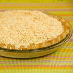 Toasted Coconut Cream Pie Recipe - A slow-cooked custard is lightened by brandied whipped cream and meringue, poured into an apricot-glazed crust, and chilled until set. Then the pie is topped with toasted coconut before serving.