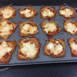 Lasagna Muffins Recipe - Individual lasagna portions can be made in muffin tins. Simply layer wonton wrappers, spaghetti sauce, and cheese for a quick and easy dinner on the go!