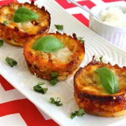 Lasagna Cupcakes Recipe - Wonton wrappers replace pasta in this lasagna recipe that delivers individual servings by baking lasagna in muffin tins.