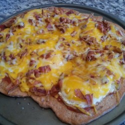 Breakfast Bacon and Sausage Pizza Recipe - Using refrigerated crescent roll for the dough, this breakfast pizza is topped with a layer of prepared salsa before being covered with scrambled eggs, bacon, slices of sausage, and Cheddar cheese.