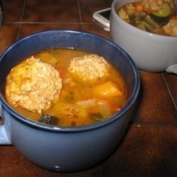 Albondigas Soup I Recipe - Rice and bite-sized meatballs made with pork and beef float in beef broth seasoned with green chili salsa, canned tomatoes, onion, garlic powder in this hearty Mexican soup for a crowd.