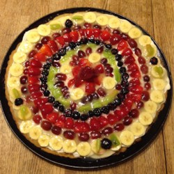 Fruit Pizza Even Better Recipe - Smooth cream cheese and fresh fruit sit atop a buttery cookie crust in this colorful dessert. The pineapple juice glaze makes a bright and sweet topping.