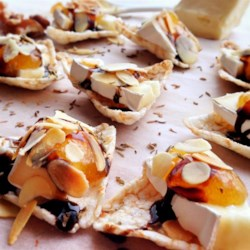 Petit Toasts with Brie, Fig, and Thyme Recipe - Impress your guests with toasts topped with Brie cheese, fig preserves, and a sprinkle of thyme at your next dinner party.