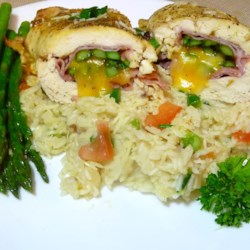 Stuffed Chicken Breasts with Asparagus and Parmesan Rice Recipe - Chicken breasts are rolled around lightly cooked asparagus with deli ham and Cheddar cheese, baked, and served on cheesy tomato-flavored rice. It's a perfect dish for spring.