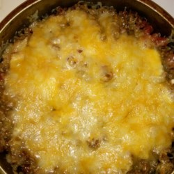 Hot Baked Taco Dip Recipe - Ground beef, tomatoes, hot taco sauce, sour cream, and Cheddar cheese are layered and cooked into a hot baked taco dip. Serve with tortilla chips!