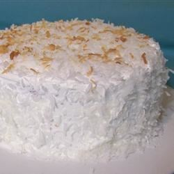 Creamy Coconut Cake Recipe and Video - This is a coconut cake that you won't have to slave over! A white cake is filled with a cream of coconut and condensed milk mixture, topped with whipped topping and finished with flaked coconut.