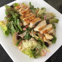 Sweet Apple-Walnut Chicken Salad Recipe - Grilled chicken is tossed with apple, candied walnuts, and blue cheese in raspberry vinaigrette to deliver a sweet topping to a large plate of salad greens.
