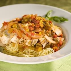 Sicilian Lemon Chicken with Raisin-Tomato Sauce Recipe - Seared lemon chicken breasts are complimented with a sweet and tangy sauce and served over angel hair pasta.  A garnish of lemon zest, shaved Parmesan cheese, and a basil sprig lends this dish a professional look.