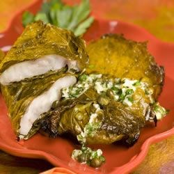 Red Snapper in Grape Leaves with Garlic and Caper butter Recipe - Red snapper fillets are encased in grape leaves before being broiled and served with a lemon butter sauce. A quick meal that is truly elegant.