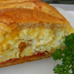 Scrambled Egg Brunch Bread Recipe - Perfect for brunch, this beautiful braid is filled with eggs, ham, and cheese. Using refrigerated crescent rolls makes it a snap to prepare.
