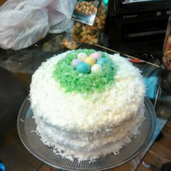Coconut Easter Cake Recipe - A pretty 3-layered coconut cake with green-tinted coconut and colorful jelly beans on top is surprisingly easy to make, thanks to using a yellow or white cake mix. Creamy coconut-flavored buttercream frosting finishes the cake in style.