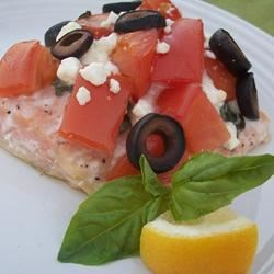 Greek-Style Baked Salmon Recipe - Topping salmon with tomatoes, onion, basil, olives, and feta cheese gives it a delicious Greek flair.