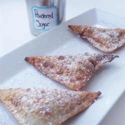 Chocolate Wontons Recipe - Crispy golden fried wonton triangles contain a sweet and molten heart of milk chocolate and strawberries. They are served warm, dusted with a little confectioners' sugar.