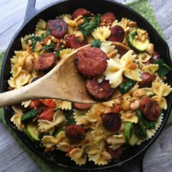 Smoked Sausage, White Bean and Spinach Pasta Recipe - Smoked sausage, white bean and spinach pasta with toasted pine nuts is the perfect weeknight meal--and it's ready in 15 minutes. The smoked sausage brings a smoky spiced flavor to the dish which means you don't need extra spices!