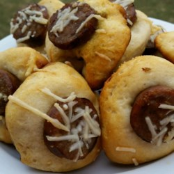 Pesto Sausage Biscuit Bites Recipe - Biscuit dough is lined with pesto and rolled around sausage links for a tasty and crowd-pleasing appetizer that will disappear quickly.