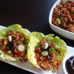 Asian Lettuce Wraps Recipe - Flavorful stir-fried pork, tofu, and green onion are rolled into a lettuce wrap with steamed rice. Serve family style at the table, and let everyone wrap their own.