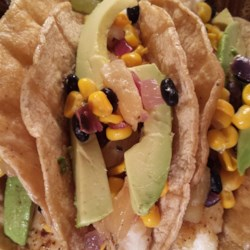 Tilapia Fish Tacos Recipe - Tilapia fish tacos layered with pineapple, black beans, corn, and avocados are a refreshing and satisfying meal the whole family will enjoy.