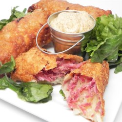 Egg Roll Reuben Wraps Recipe - Fill egg roll wrappers with the ingredients usually found in an Reuben sandwich for a unique and tasty finger food for your next gathering.