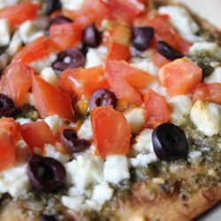 Mediterranean Pesto Pizza Recipe - This pesto pita pizza topped with feta cheese, Kalamata olives, and tomatoes is a Mediterranean-inspired version of pizza. Try making a naan-based pizza too!