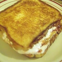 Gooey Toasted PB and J's Recipe - Toasted peanut butter, jelly, and marshmallow cream sandwiches are super easy to prepare - but yummy and just dressed up enough for a romantic dinner for two.