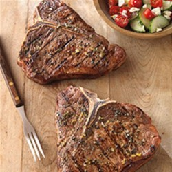Greek-Seasoned T-Bone Steaks with Cucumber and Tomato Salad Recipe - Who said impressive dishes have to be complicated? Iconic T-Bone Steak is grilled then sliced and served with a simple Greek salad.