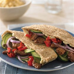Greek-Style Beef Pita Recipe - Stir-fried beef is stuffed into pitas and topped with your family's favorite veggies like cucumbers and olives.
