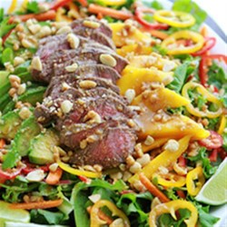 Easy Sirloin Thai Salad Recipe - Tender Sirloin on a bed of crisp salad greens and fresh mango paired with avocado and bell peppers. All topped with a delicious Thai dressing.