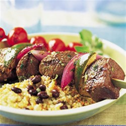Mojo Beef Kabobs Recipe - Cubes of steaks are threaded on skewers with lime and onion then grilled to perfection. A sauce of citrus, herbs and spices provides the finishing touch.
