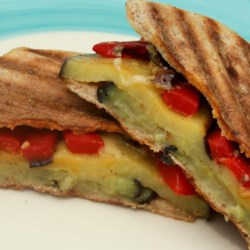 Eggplant Panini Recipe - Baby eggplant, roasted red peppers, and mozzarella cheese are a tasty trio in this crispy panini that is perfectly paired with a green salad and glass of wine.