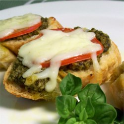 Basil Pesto Bread Recipe - A simple pesto is spread on Italian bread slices and layered with roma tomatoes and cheese, then broiled.